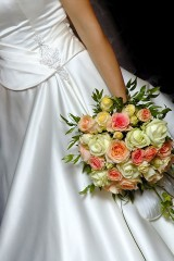 a bride, wearing a white wedding dress and holding a beautiful bridal bouquet