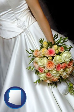 a bride, wearing a white wedding dress and holding a beautiful bridal bouquet - with Arizona icon