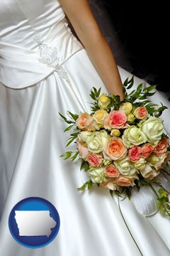 a bride, wearing a white wedding dress and holding a beautiful bridal bouquet - with Iowa icon