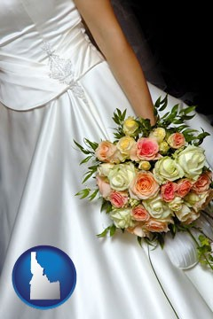 a bride, wearing a white wedding dress and holding a beautiful bridal bouquet - with Idaho icon