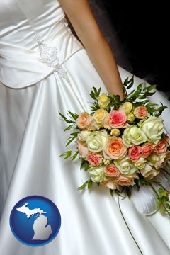 a bride, wearing a white wedding dress and holding a beautiful bridal bouquet - with Michigan icon