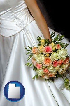 a bride, wearing a white wedding dress and holding a beautiful bridal bouquet - with Utah icon